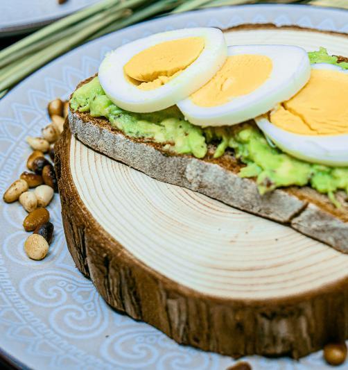 Roggenbrot mit Avocado, Pinienkernen und gekochtem Ei